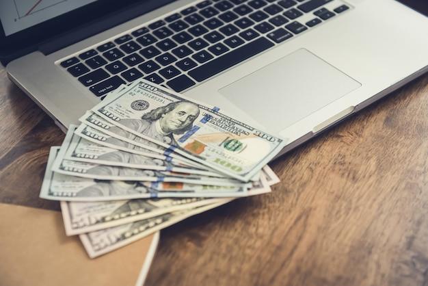 Pieniądze, dolary amerykańskie, na komputerze przenośnym przy stole roboczym