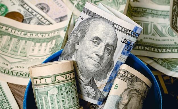 Pieniądze dolary amerykańskie otwarty groszowy bank w kształcie butli gazowej z banknotami dolarowymi