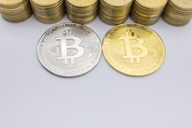Pieniądze, finanse, handel elektroniczny i kryptowaluty. zamyka up srebna i złota bitcoin moneta z stosem.
