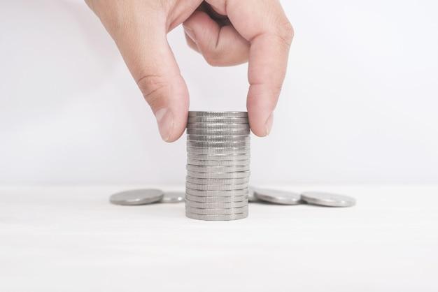 Pieniądze, finanse, koncepcja rozwoju biznesu, ręka mężczyzny wkładająca monety pieniężne do stosu monet