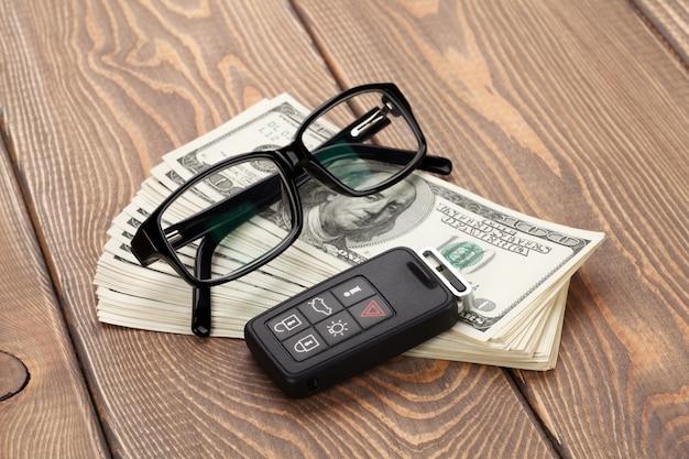 Pieniądze gotówka, okulary i kluczyk samochodowy na drewnianym stole