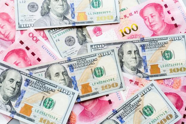 Pieniądze gotówkowe: sto dolarów amerykańskich i sto chińskich juanów