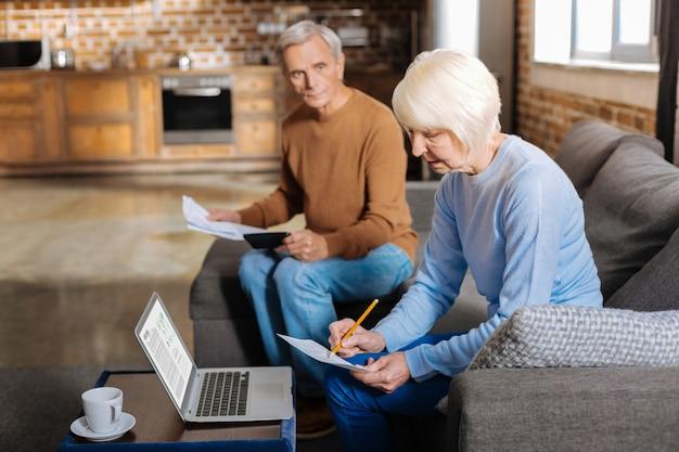 Pieniądze i finanse. wesoła miła pozytywna kobieta uśmiecha się i robi notatki podczas planowania budżetu rodzinnego