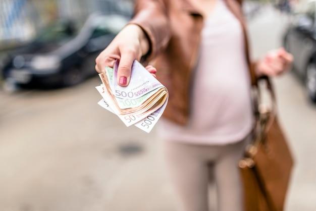 Pieniądze i finansów pojęcie, kobieta daje pieniądze