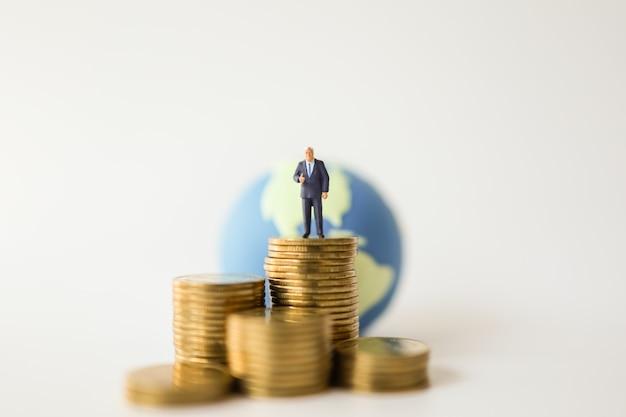 Pieniądze i globalna koncepcja biznesowa. biznesmen miniaturowe postacie ludzi stojących na stosie złotych monet i mini kuli świata jako tło.