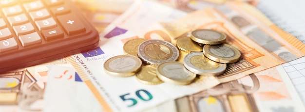 Pieniądze i kalkulator danych finansowych z wykresami i liczbami.