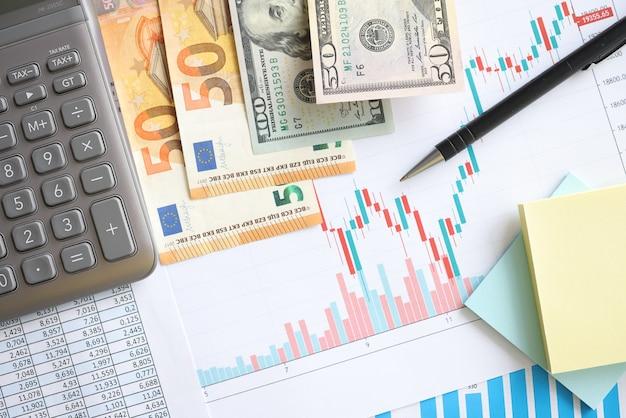 Pieniądze i kalkulator leżące na dokumentach z zbliżeniem wykresu