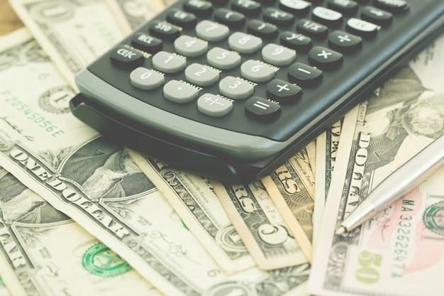 Pieniądze i kalkulator na pasku danych finansowych