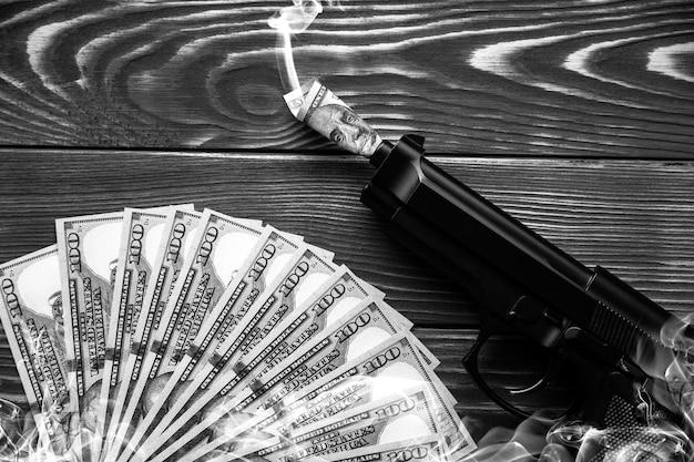 Pieniądze i pistolet leżący na drewnianym tle. dolary rządzą światem. skorumpowany świat. zabijanie z chciwości.