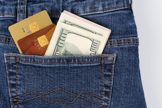 Pieniądze i plastikowe karty kredytowe w kieszeni dżinsów