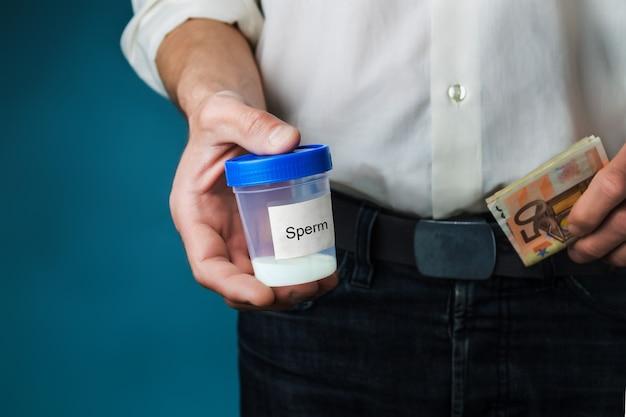 Pieniądze i pojemnik ze spermą w rękach człowieka. koncepcja oddawania nasienia