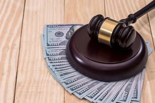 Pieniądze i sędziowie młotkiem na drewnianym stole