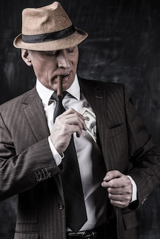Pieniądze i władza. poważny starszy mężczyzna w kapeluszu i szelkach palący cygaro i chowający pieniądze do kieszeni, stojąc na ciemnym tle
