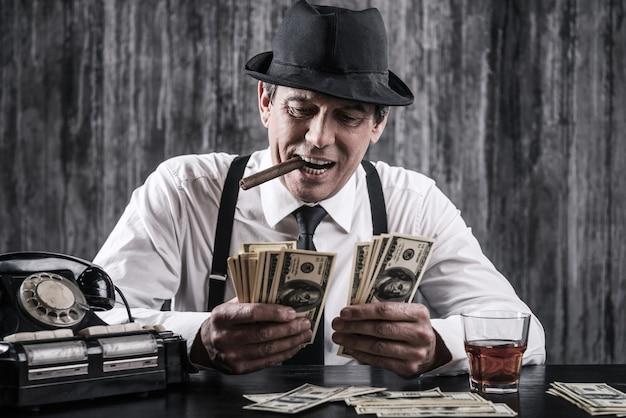 Pieniądze i władza. starszy gangster w koszuli i szelkach liczący pieniądze i uśmiechający się siedząc przy stole