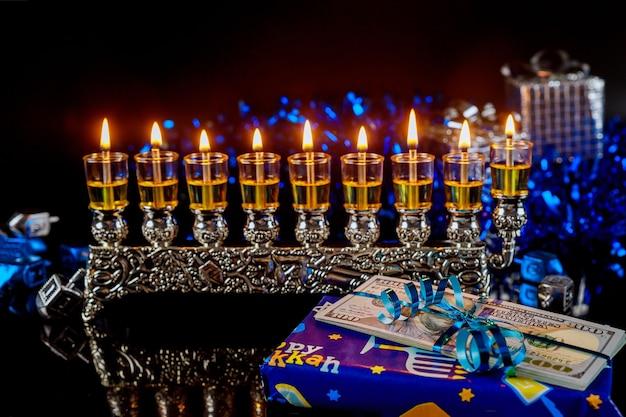 Pieniądze jako prezent z menorą na chanukę na czarnej powierzchni. żydowska tradycja świąteczna.