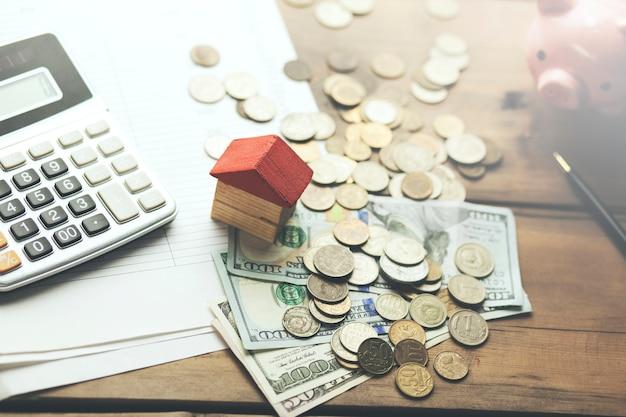 Pieniądze, kalkulator i skarbonka na stole