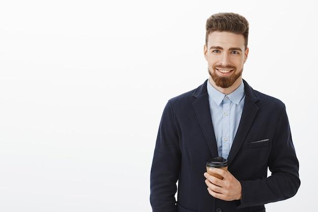 Pieniądze lubią zaufanie. pewny siebie, charyzmatyczny i inteligentny przystojny mężczyzna z brązowymi włosami, brodą i niebieskimi oczami trzymający papierowy kubek z kawą uśmiechnięty radośnie spotykający uroczą dziewczynę po pracy w kawiarni