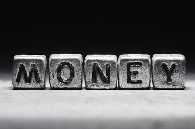 Pieniądze napis na metalowych kostkach w stylu grunge na czarnym tle na białym tle