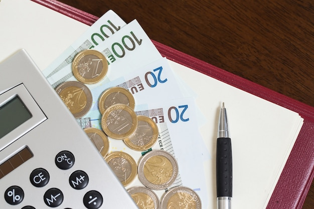Pieniądze, notatnik i kalkulator na stole