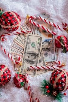 Pieniądze papierowe dolarów na białym tle z rekwizyty świąteczne. nowy rok i boże narodzenie i finanse.