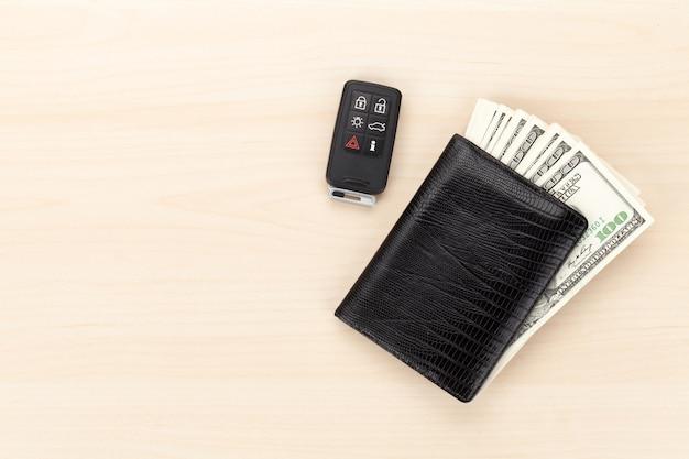 Pieniądze portfel i kluczyk samochodowy na drewnianym stole. widok z góry z miejscem na kopię