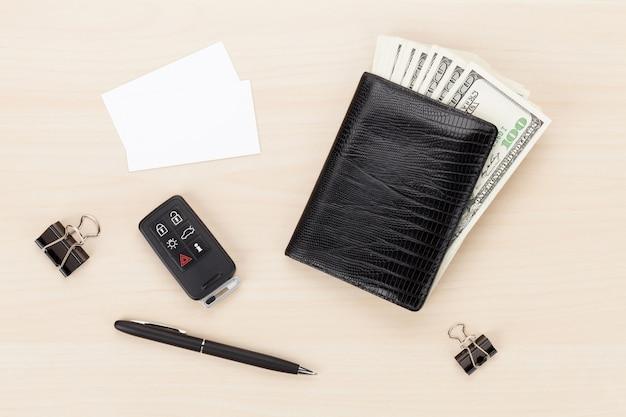 Pieniądze portfel i kluczyk samochodowy na drewnianym stole. widok z góry z wizytówkami na miejsce na kopię