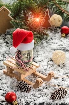 Pieniądze prezent na boże narodzenie i płatki śniegu na drewnianym stole