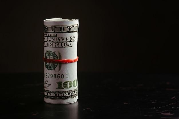 Pieniądze roll dolarów na czarnym tle.