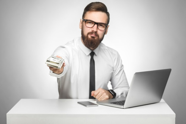 Pieniądze są twoje! portret przystojny bogacz brodaty młody duży szef w białej koszuli i czarnym krawacie siedzi w biurze, dając dużo pieniędzy, bonus, patrząc na kamerę, na białym tle, kryty
