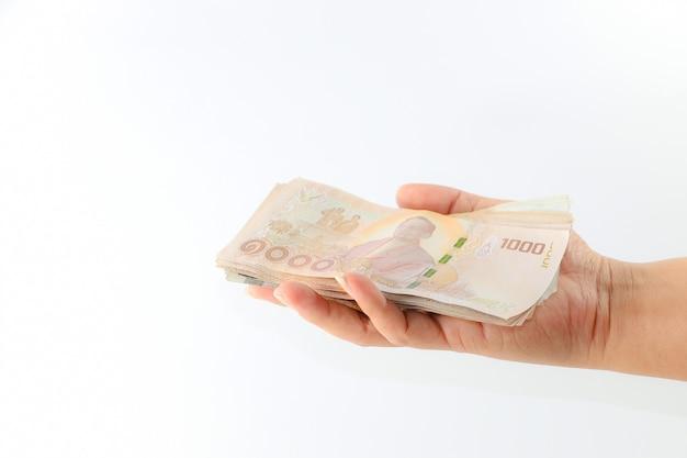 Pieniądze tajlandzki baht na ręce odizolowywającej na białym tle
