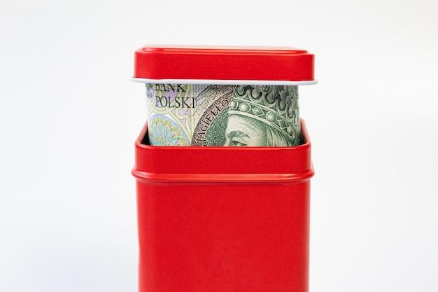 Pieniądze w czerwonym pudełku, skarbonka, złoty polski, z bliska, odizolowane, sto złotych