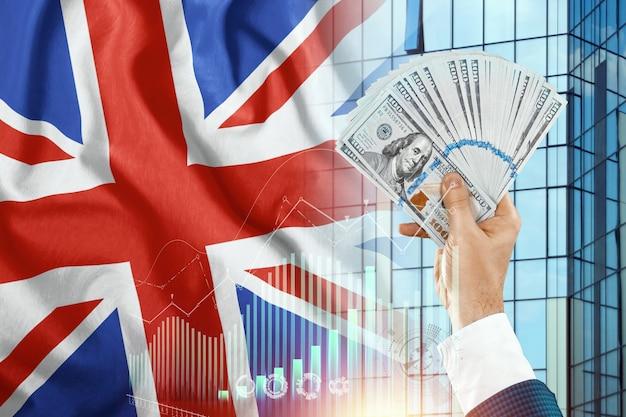 Pieniądze w dłoni mężczyzny na tle flagi anglii.
