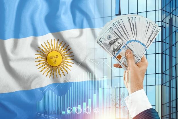 Pieniądze w dłoni mężczyzny na tle flagi argentyny.