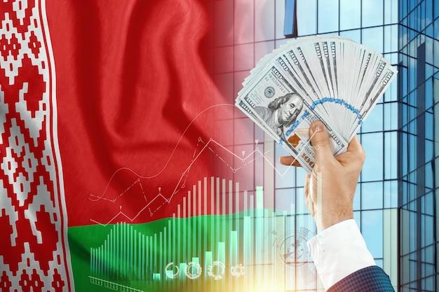 Pieniądze w dłoni mężczyzny na tle flagi białorusi.