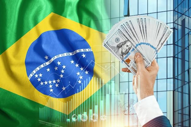 Pieniądze w dłoni mężczyzny na tle flagi brazylii.