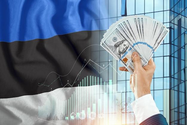Pieniądze w dłoni mężczyzny na tle flagi estonii.