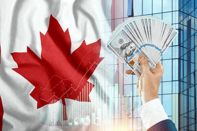 Pieniądze w dłoni mężczyzny na tle flagi kanady