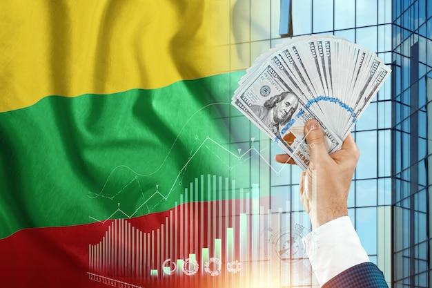 Pieniądze w dłoni mężczyzny na tle flagi litwy.