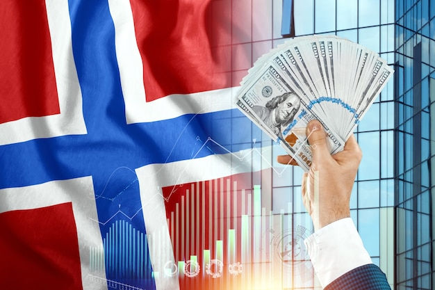 Pieniądze w dłoni mężczyzny na tle flagi norwegii