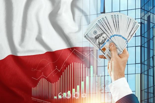 Pieniądze w dłoni mężczyzny na tle flagi polski.
