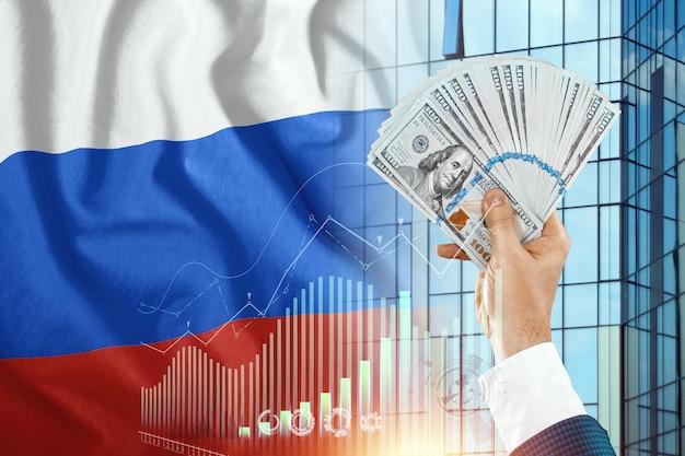 Pieniądze w dłoni mężczyzny na tle flagi rosji