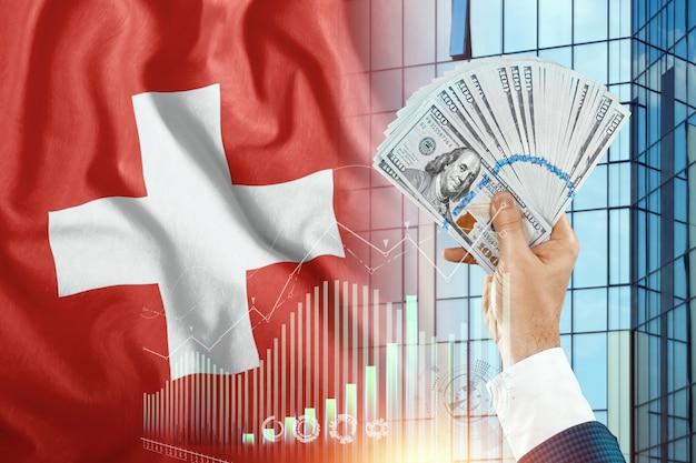 Pieniądze w dłoni mężczyzny na tle flagi szwajcarii.