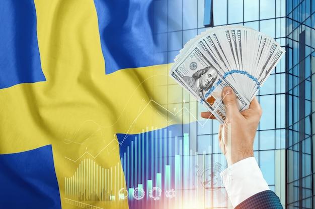 Pieniądze w dłoni mężczyzny na tle flagi szwecji.