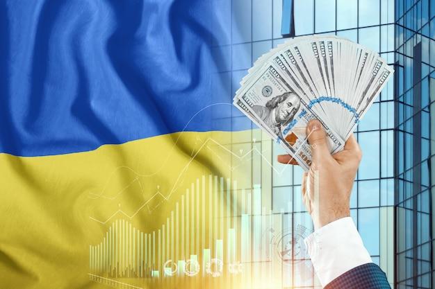 Pieniądze w dłoni mężczyzny na tle flagi ukrainy