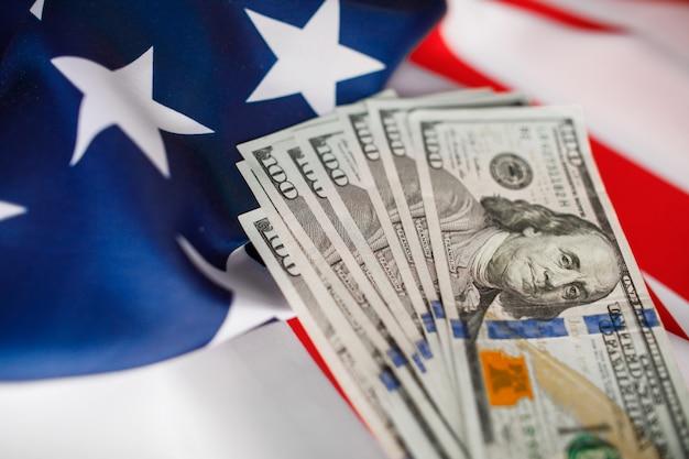 Pieniądze w dolarach amerykańskich. sto dolarów banknotów z bliska na tle flagi usa
