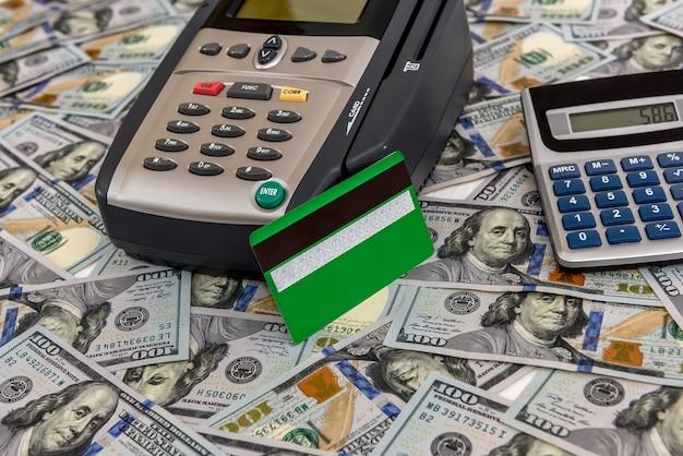 Pieniądze w dolarach na terminal bankowy i kalkulator