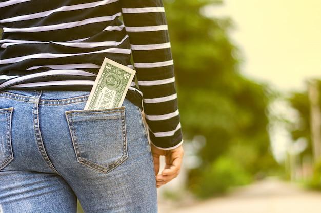 Pieniądze w kieszeni kobiety. - kup i oszczędzaj na przyszłej koncepcji.