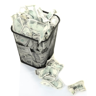 Pieniądze w koszu na śmieci na białym tle