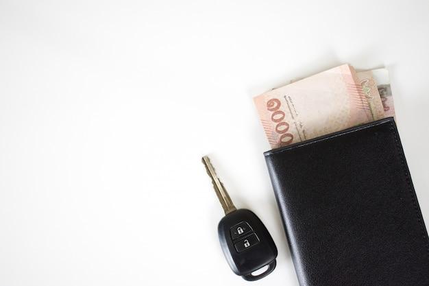Pieniądze w portfelu z widokiem z góry kluczyki do samochodu