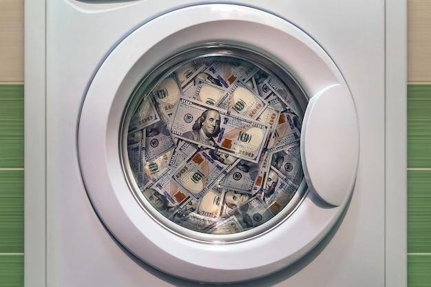 Pieniądze w pralce z bliska. pojęcie prania nielegalnych pieniędzy. pranie brudnych amerykańskich banknotów o nominale sto dolarów